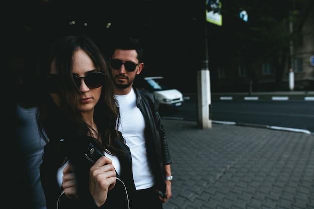 Um casal vestido de preto e branco com óculos de sol nos olhos na cidade. história de amor de rua