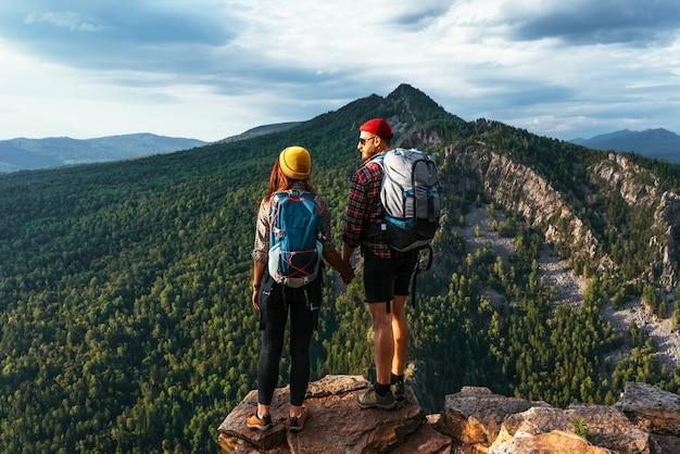 Um casal viajando em equipamento de caminhada nas montanhas ao pôr do sol. dois turistas no topo da montanha. um homem e uma mulher nas montanhas. caminhadas nas montanhas com mochilas. dois viajantes