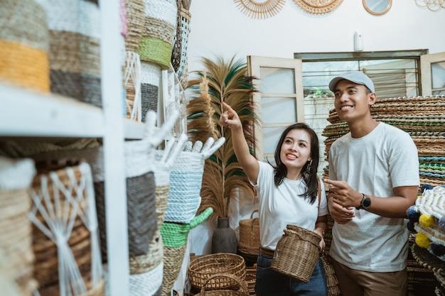 Um casal visualizando e selecionando artesanato com o dedo apontando entre os itens de artesanato na galeria de artesanato