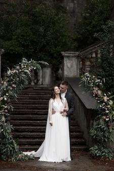 Um casamento em uma antiga villa de um casal feliz de noivos arco de casamento redondo decorado com flores brancas