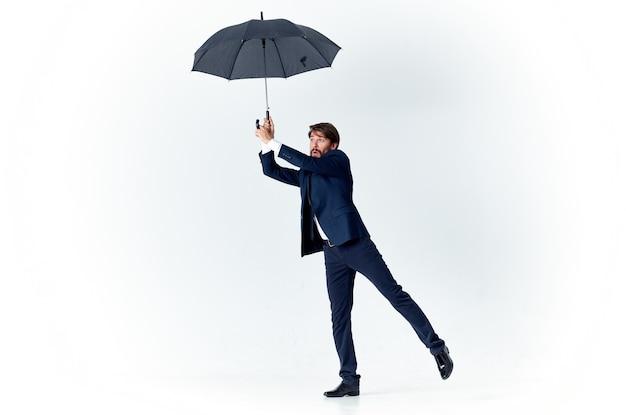 Um cavalheiro com um guarda-chuva aberto em um terno escuro curvado para o lado