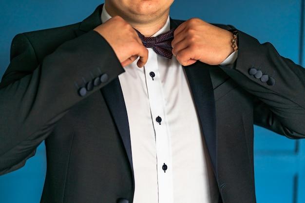 Um cavalheiro de luxo em uma jaqueta preta e camisa branca corrige a gravata borboleta por suas mãos