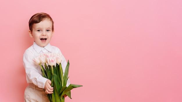 Um cavalheiro de menino feliz tem um buquê de delicadas tulipas cor de rosa nas mãos. espaço para o seu texto, copie o espaço
