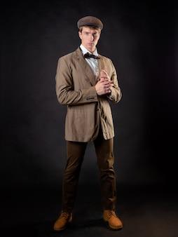 Um cavalheiro inteligente no estilo vitoriano. terno retrô vintage, jovem atraente de colete e gravata borboleta, com um boné na cabeça