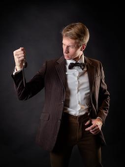 Um cavalheiro inteligente no estilo vitoriano. terno retrô vintage, jovem atraente de colete e gravata borboleta, ele segura um relógio de bolso em uma corrente na mão