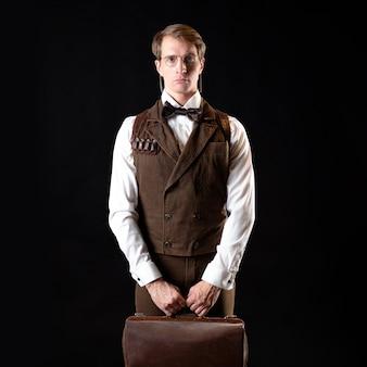 Um cavalheiro inteligente no estilo vitoriano. terno retrô vintage, jovem atraente em um colete e gravata borboleta, ele segura sua bolsa nas mãos
