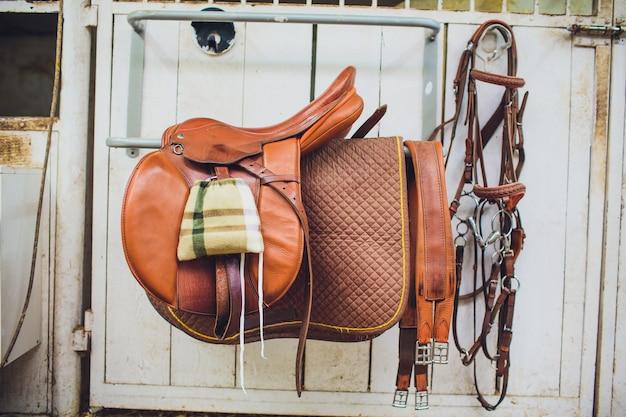 Um cavalo de sela de couro em um estábulo