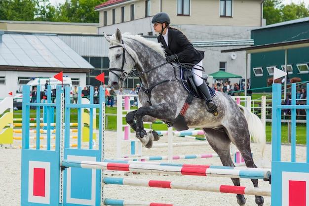 Um cavalo em equipamento esportivo com um cavaleiro na sela pula a barreira em uma competição de saltos.