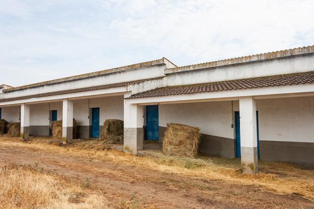Um celeiro sem paredes com fardos de palha dentro.