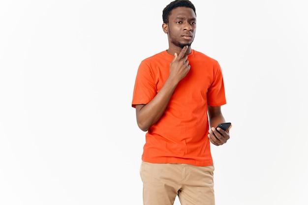 Um celular na mão de um homem de aparência africana em um fundo claro e uma camiseta laranja