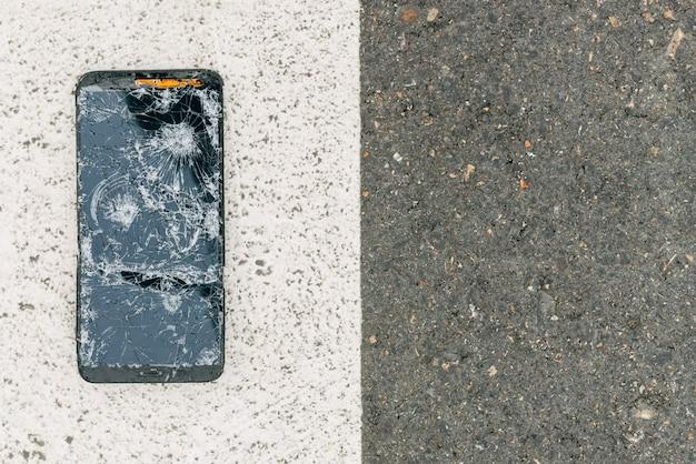 Um celular quebrado no meio da rua, no topo de uma passagem para pedestres, com um lado da imagem branco e o outro preto