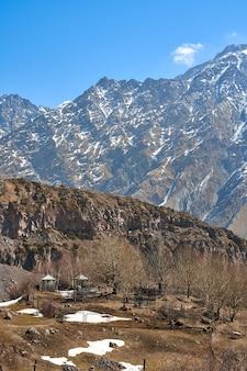 Um cemitério em uma colina em um vale de montanha. altas montanhas cobertas de neve ao fundo.