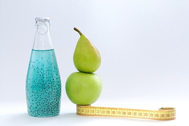 Um centímetro, uma maçã, uma pêra e garrafas de vidro com semente de manjericão azul ficar em um fundo branco
