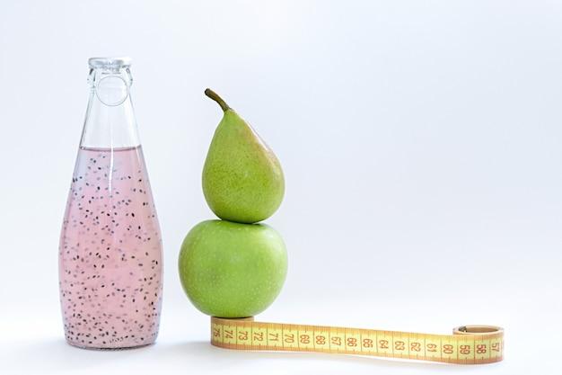 Um centímetro, uma maçã, uma pêra e garrafas de vidro com semente de manjericão rosa ficar em um fundo branco