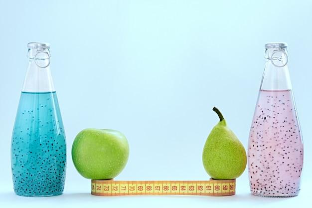 Um centímetro, uma maçã, uma pêra e garrafas de vidro com sementes de manjericão de cor rosa e azul ficar sobre um fundo azul