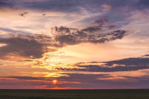 Um céu colorido e pitoresco acima do campo durante o pôr do sol_
