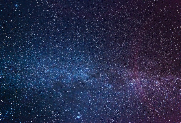 Um céu estrelado deslumbrante em uma noite de inverno sem nuvens em meio a uma névoa rosa-azulada que brilha acima da terra