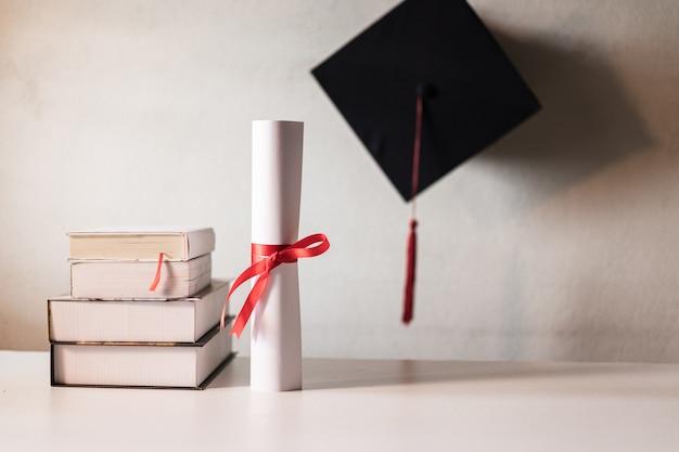 Um chapéu de formatura ou papelão e certificado de diploma amarrado com fita vermelha em uma pilha de livros com espaço vazio ligeiramente saturado com vinheta para efeito vintage