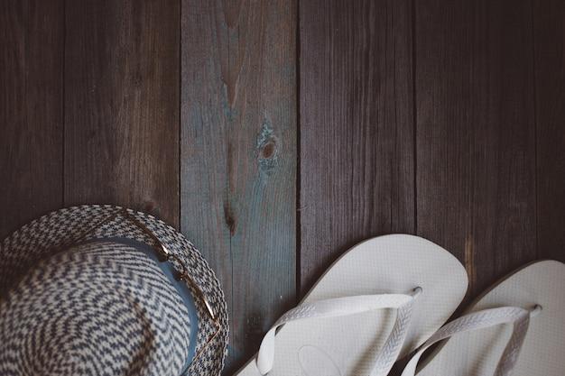 Um chapéu, óculos escuros e chinelos brancos sobre o fundo de madeira