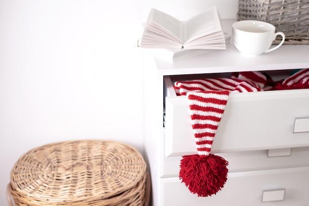 Um chapéu vermelho-branco com um grande pompom vermelho está pendurado em uma gaveta aberta de uma cômoda branca.