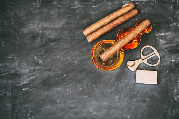 Um charuto, um cinzeiro, uma tesoura de cigarro, um isqueiro numa mesa de concreto escuro.