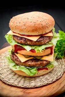 Um cheeseburger duplo de estilo clássico com dois hambúrgueres de carne, molho, alface, queijo, picles e cebola em um pão de gergelim