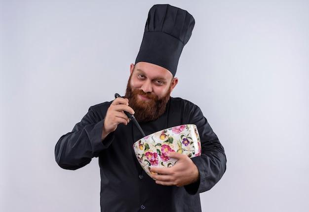 Um chef barbudo confiante de uniforme preto segurando uma enorme xícara de flores com uma concha enquanto olha para a câmera em uma parede branca