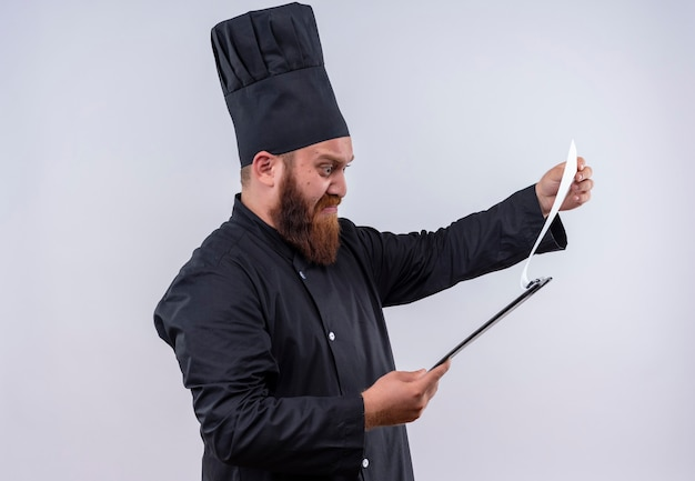 Um chef barbudo confuso, de uniforme preto, pensando como se estivesse olhando para uma lista em uma parede branca