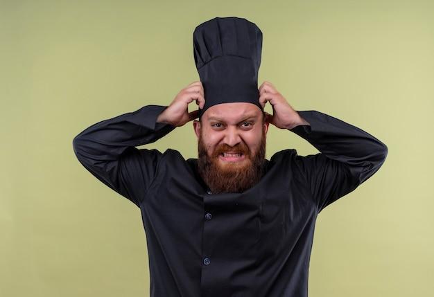 Um chef barbudo descontente em uniforme preto expressando negatividade com as mãos na cabeça enquanto olha para uma parede verde