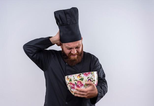 Um chef barbudo descontente em uniforme preto segurando uma enorme xícara de flores e olhando para ela com expressão negativa em uma parede branca