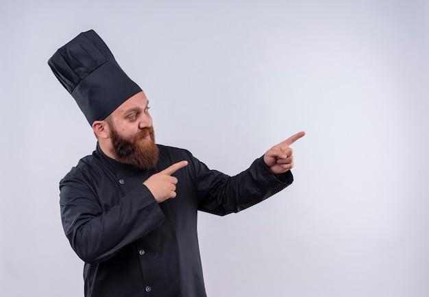 Um chef barbudo feliz em uniforme preto apontando para o lado direito com o dedo indicador enquanto olha para o lado em uma parede branca