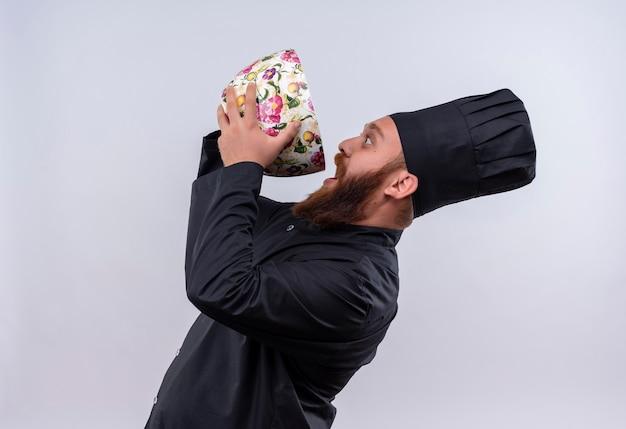 Um chef barbudo feliz em uniforme preto bebendo de um copo floral enorme em uma parede branca