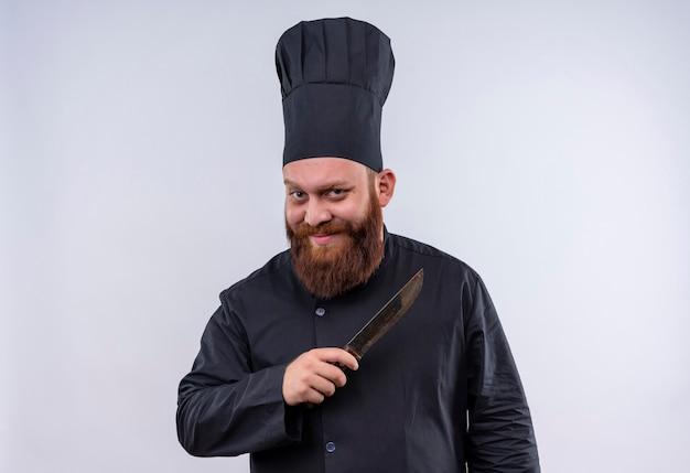 Um chef barbudo, positivo e engraçado, de uniforme preto, segurando uma faca enquanto olha para a câmera em uma parede branca