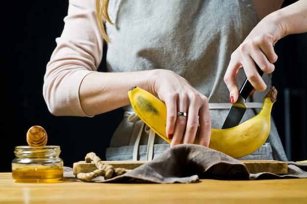 Um chef corta uma banana em fatias. cozinhar bananas fritas.