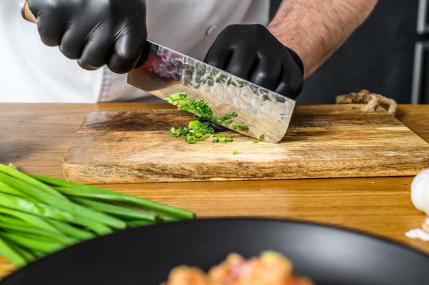 Um chef de luvas pretas está cortando cebolas verdes frescas em uma tábua de madeira.