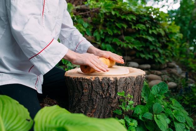 Um chef de restaurante de uniforme desenrola a massa em um toco na floresta