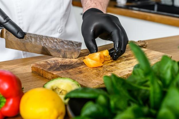 Um chef em luvas pretas está cortando tomates em uma tábua de madeira