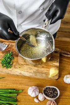 Um chef em luvas pretas prepara legumes salteados. conceito de cozinhar alimentos orgânicos saudáveis