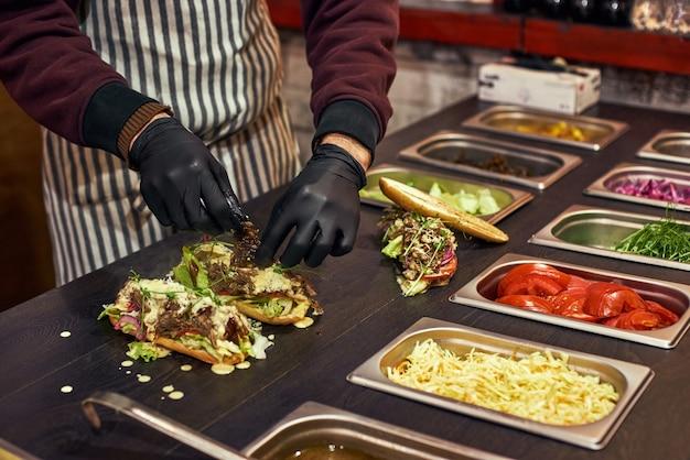 Um chef preparando um sanduíche com salada fresca. cort de comida da feira de rua. cozinha ao ar livre