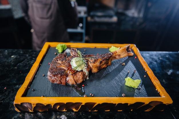 Um chef profissional serve lindamente um suculento bife grelhado com manteiga e temperos. carne grelhada em restaurante.