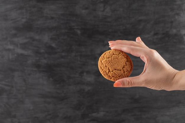 Um chef segurando biscoitos de aveia na mão.