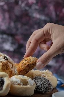 Um chef segurando biscoitos de manteiga por lado.