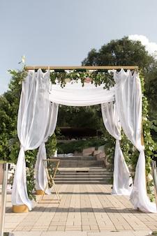 Um chuppah festivo decorado com lindas flores frescas para uma cerimônia de casamento ao ar livre