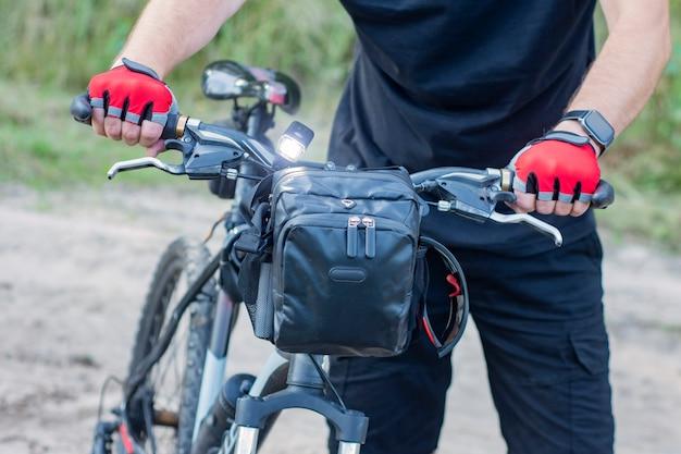 Um ciclista com luvas perto de uma mountain bike com uma bolsa no guiador.