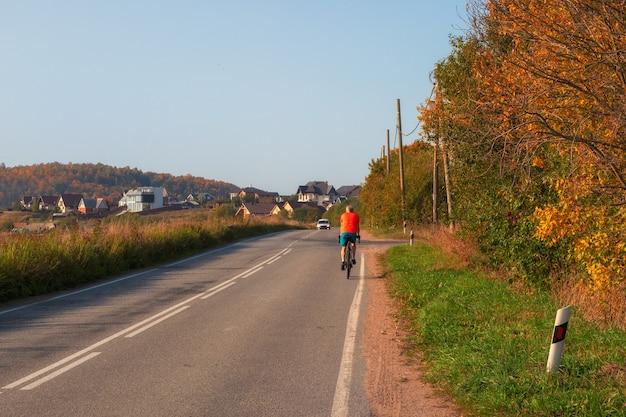 Um ciclista do sexo masculino em uma estrada rural de outono.