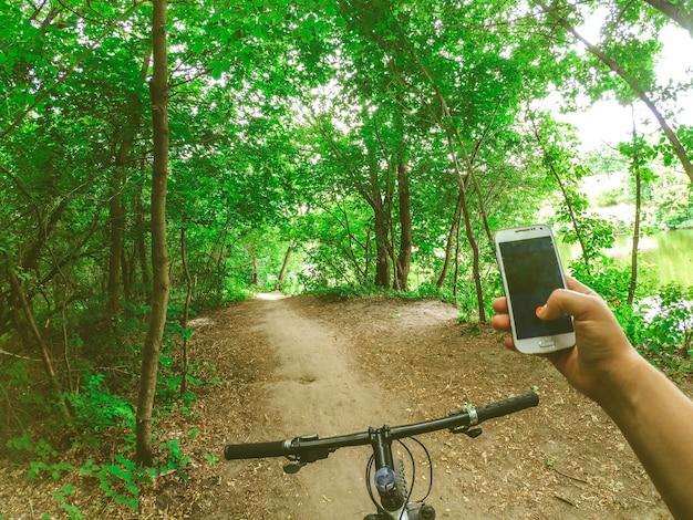 Um ciclista parado na floresta em uma estrada de terra com um telefone