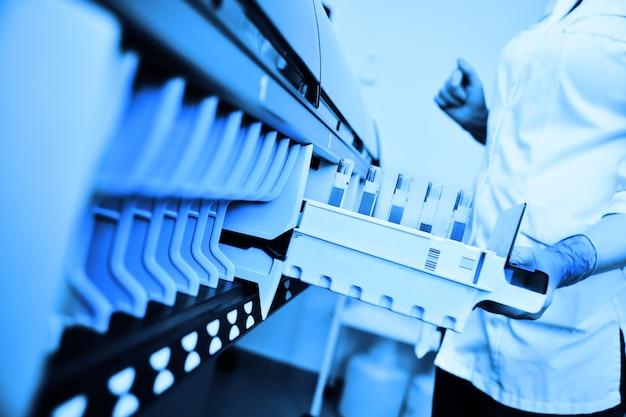 Um cientista em um laboratório coloca tubos de ensaio com sangue ou urina no recipiente de um analisador térmico. equipamento médico informatizado moderno