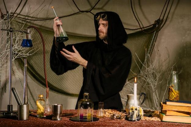 Um cientista medieval, um alquimista, mede as temperaturas em um frasco em seu laboratório.