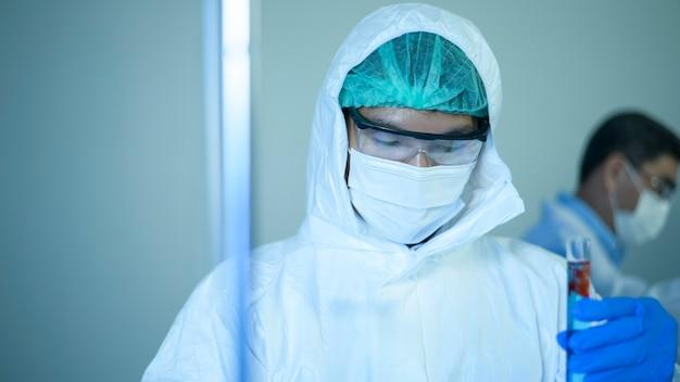 Um cientista segurando um tubo químico líquido no conceito de saúde de laboratório, ciência e tecnologia