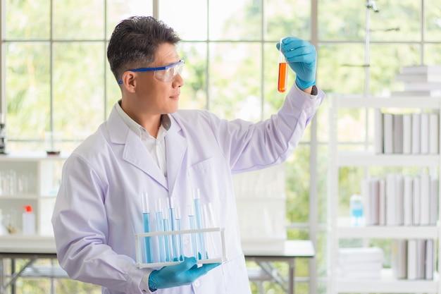 Um cientista tailandês asiático usava um vestido branco e óculos de proteção, olhando para um tubo de ensaio contendo produtos químicos laranja e analisando os resultados do experimento em laboratório.